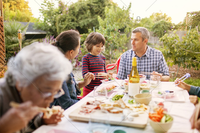 Family eating food on picnic table at backyard