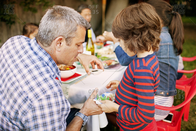 Father serving food to son on picnic table in backyard