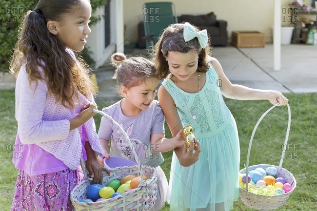 Happy sisters carrying Easter baskets at yard