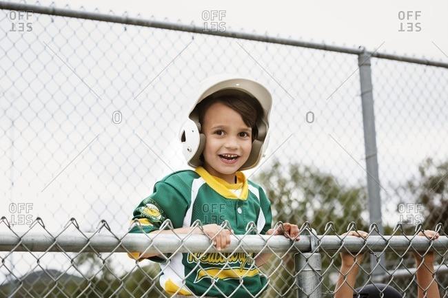 Portrait of cheerful boy in baseball uniform against clear sky