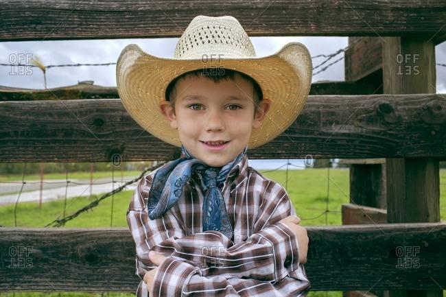 Portrait of happy boy wearing cowboy hat on field