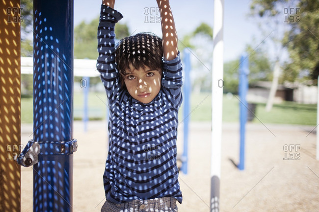 Portrait of boy hanging from outdoor play equipment at playground