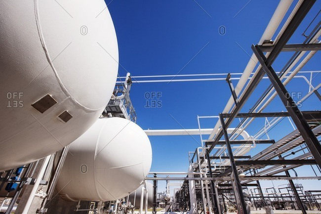 Natural gas tanks in oil refinery against clear sky