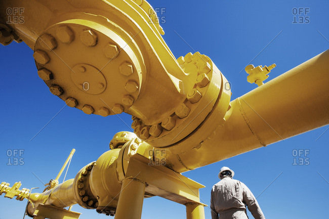 Male worker standing below yellow painted pipeline at oil refinery