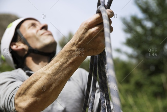 Close-up of mature man holding climbing rope