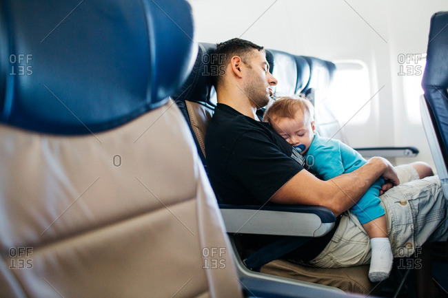 Dad and baby sleeping on plane