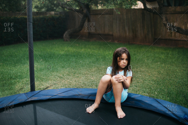 Girl sitting quietly on trampoline