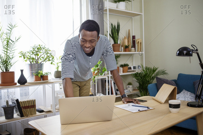 Happy man using laptop at table in home office