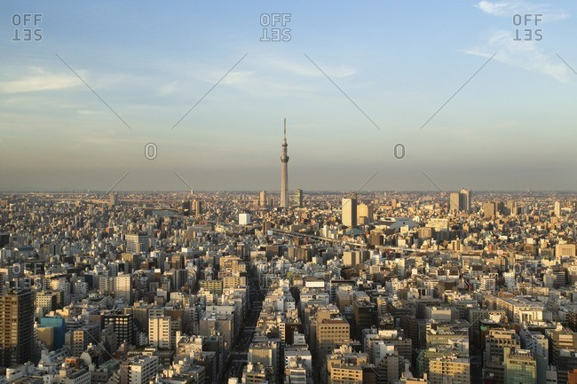 Communications tower amidst cityscape against sky