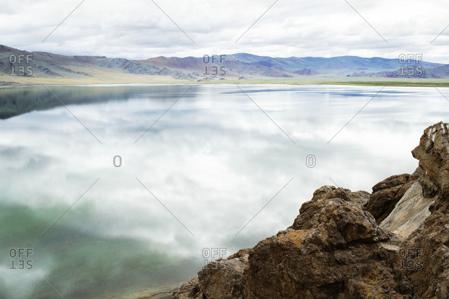Scenic view of calm lake and mountains against sky