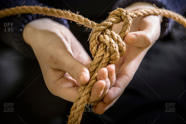 Nautical student tying sheet bend knot with rope
