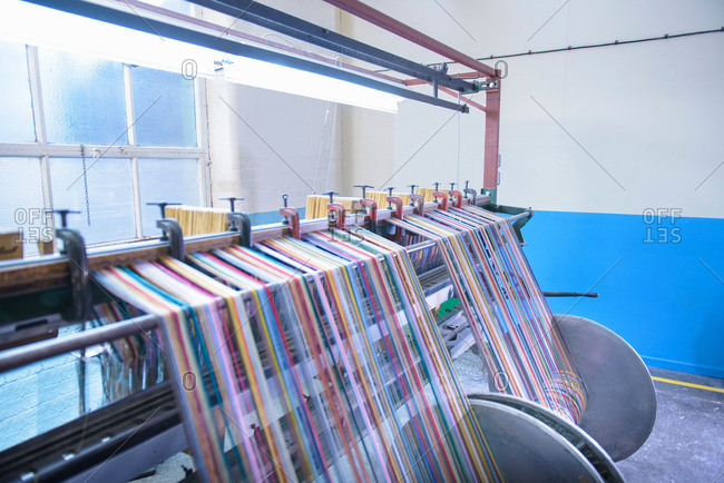 Multicolored threads on industrial loom in textile mill