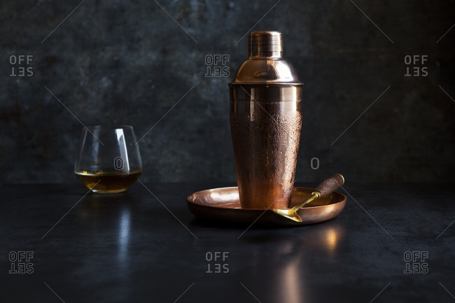 Copper cocktail shaker and a glass of whisky