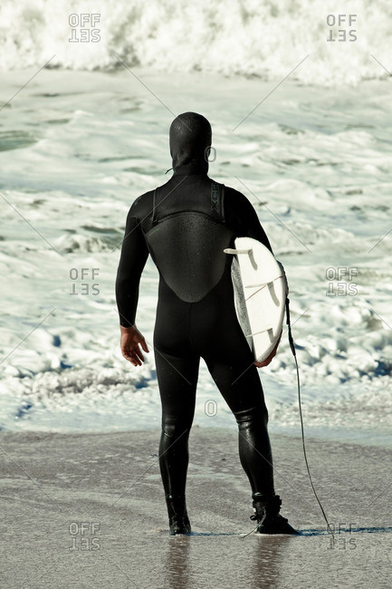 January 5, 2011: Surfer in a wetsuit looking out at the ocean waves