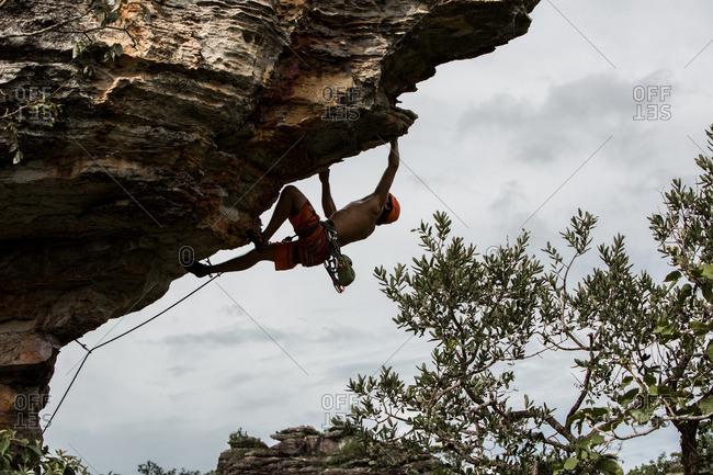 Man climbing up a cliff in Brazil