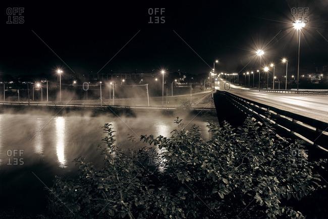 City street lights illuminated above a river and bridge in Brasilia, Brazil
