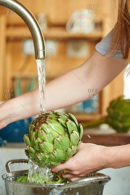 A woman washing a globe artichoke under a kitchen tap