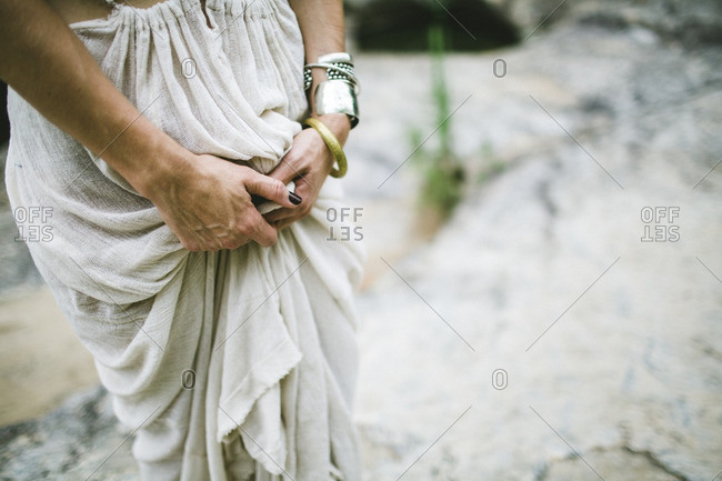 Close up of a woman's hands holding her gauze dress in bunch