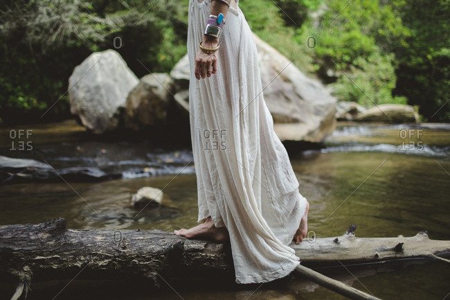 Woman in gauze dress walks on log across stream