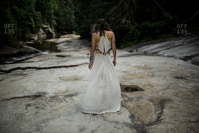 Back view of woman in long gauze dress walking on rocks by stream