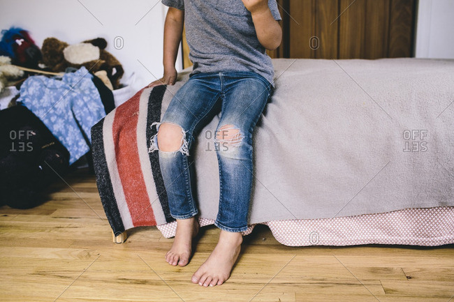 Child in pair of ripped jeans sitting on bed