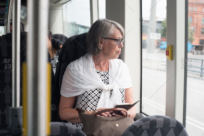 Older woman riding on a bus looking out the window
