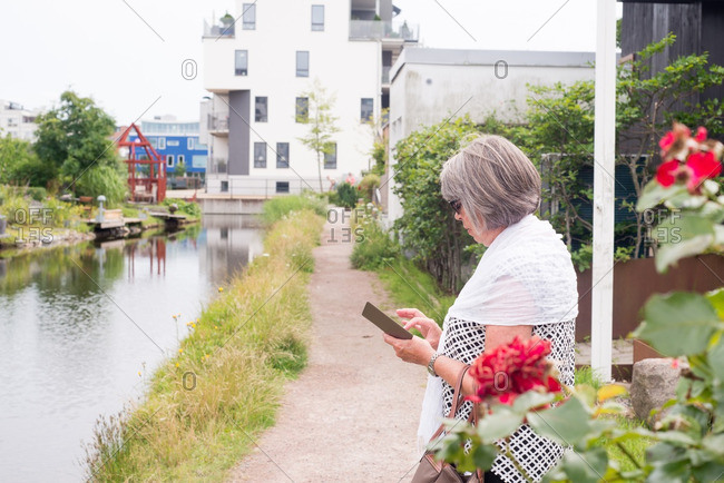 Older woman standing by a river while texting on her cell phone