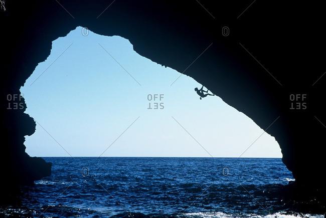 Climber hanging from coastal rocks
