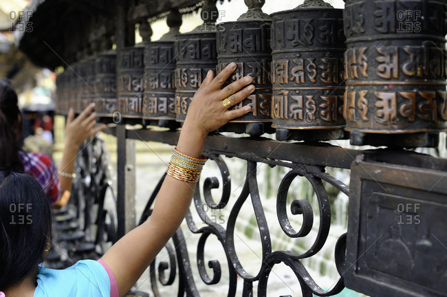 Person touching Buddhist prayer wheel