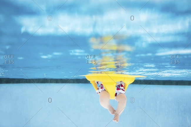 Underwater view of baby's legs in a float