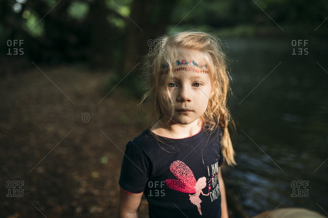 Portrait of a girl standing on the edge of a riverbank
