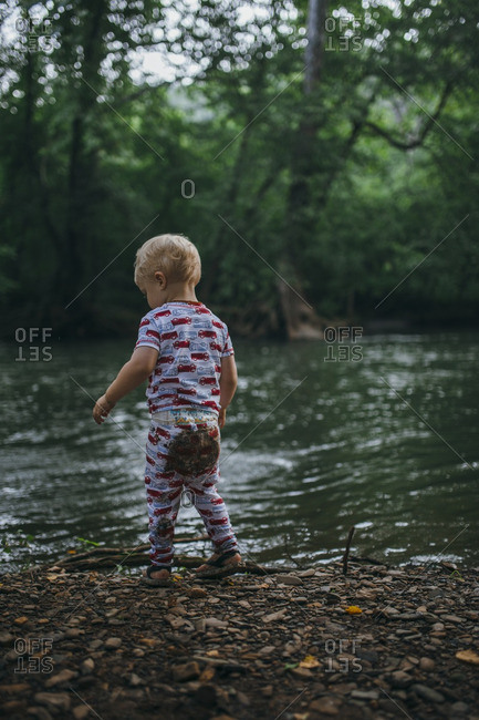 Toddler boy playing on the edge of a riverbank