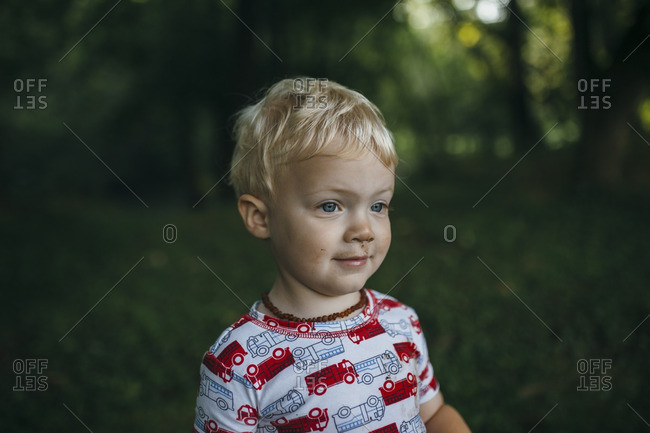 Portrait of a blonde toddler boy outside