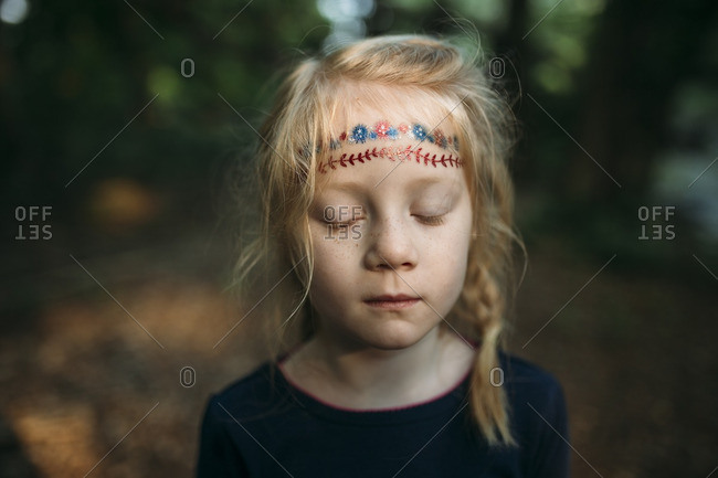 Portrait of a girl with firework tattoos on her forehead