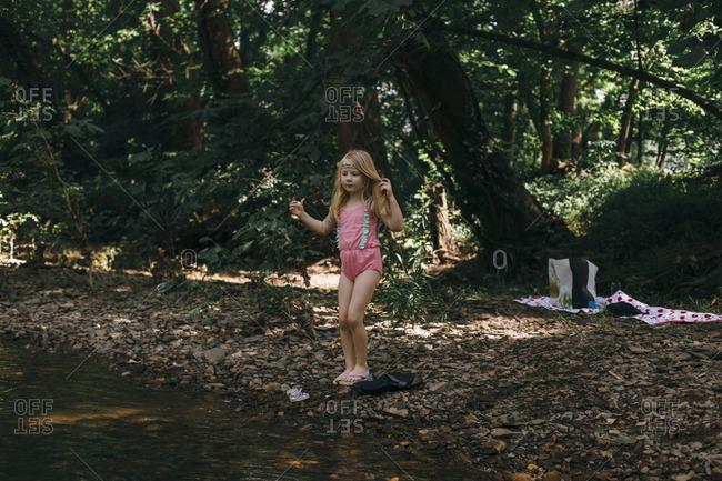 Girl preparing to swim in a river