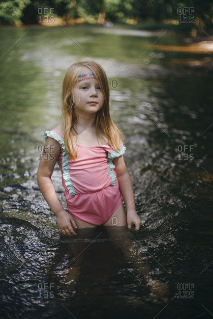 Little girl standing in a river