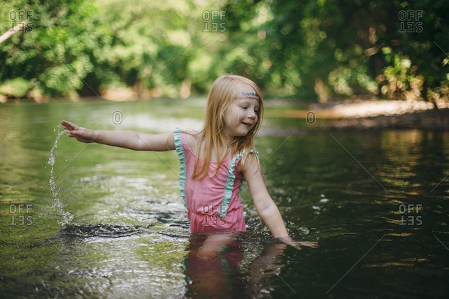 Little girl swinging arms in the river water