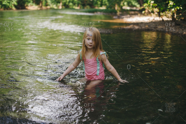 Little girl swimming in a river