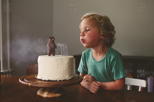 Little blonde boy blowing out birthday candles