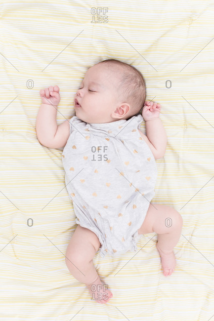 Baby sleeping on a soft yellow striped blanket