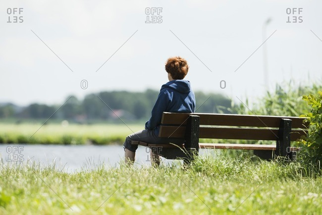 Middle-aged woman sitting on a bench overlooking the water in Leiden Zuid-Holland, Netherlands