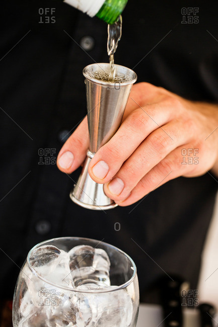Man pouring alcohol into a jigger for a cocktail