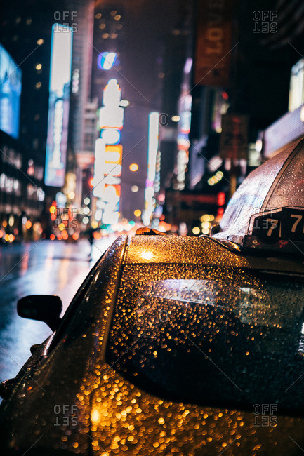 Close-up of water droplets on a taxi cab in the city at night