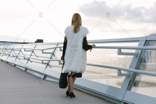 Woman dressed in a fur coat standing along an elevated walkway in the city