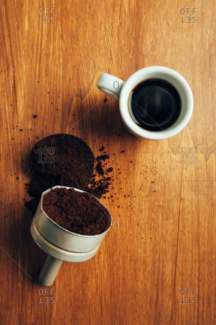 Overhead view of a cup of coffee next to an espresso funnel filled with coffee grinds
