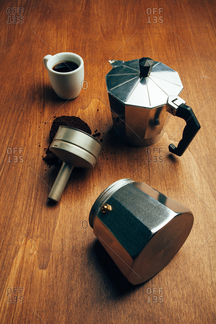 Stovetop espresso maker next to a cup of coffee