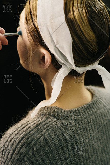 Hand applying eye shadow to woman's eyes