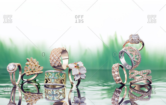 Sparkly fashion rings stacked on top of water