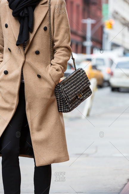 Woman walking on city street carrying black and white purse
