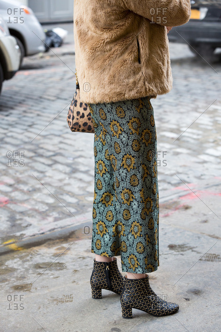 Woman on city street wearing floral pants and fur coat